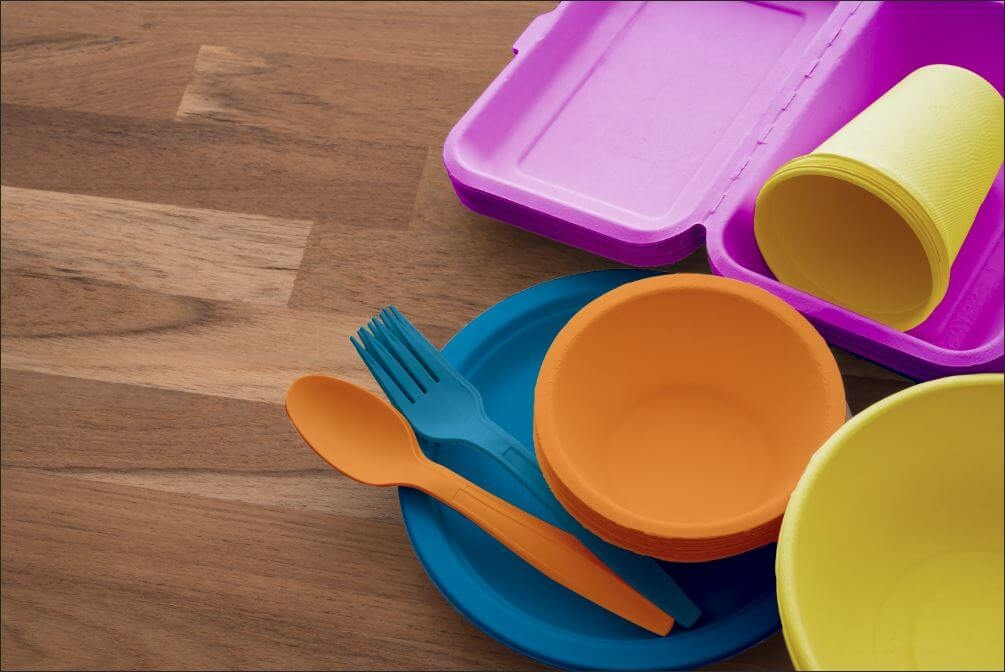 Colorful disposable dishes, plates, cups, bowls, utensils and to-go boxes
